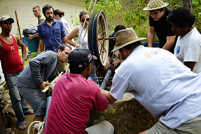 Team of primitive engineers with The Herbal Medic team working on a pulley system.