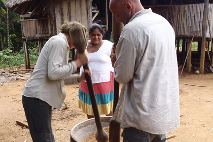A native villager teaching how to pound grain out by hand