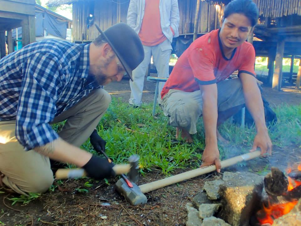 Teaching primitive blacksmithing to a native man